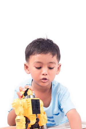 Portrait of cute child asian little boy playing robot toy Stock Photo - 66665545