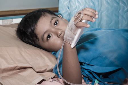 Little boy sick lying on patient  bed,hand in saline