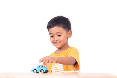 Cute asian boy play toy blur car