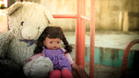 doll sad with teddy bear ,vintage tone