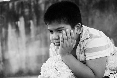 Cute asian boy crying alone in the park ,black and white tone Stock Photo