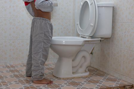 poco niño asiático orina en el inodoro Foto de archivo