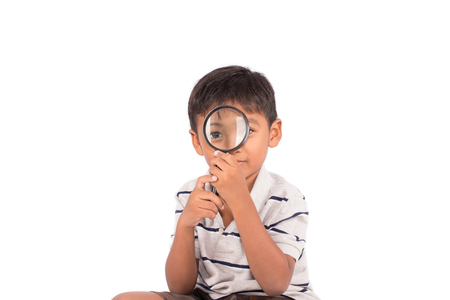 attentive: Cute asian little boy play magnifying glass
