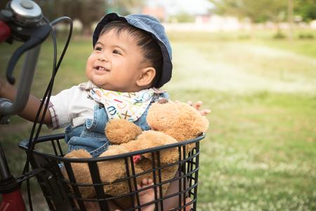 Cute asian baby sitting in bicycle basket,vintage tone