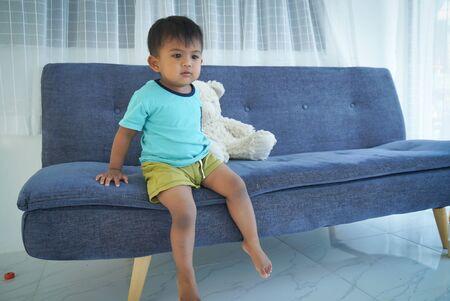 Cute little boy sitting on the sofa with teddy bear