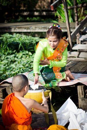 alms: The women in Thai dress give alms to monks in Ladkrabang, Bangkok, Thailand Editorial