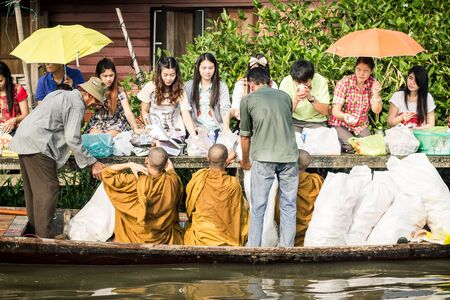 limosna: Many people give alms to monks in Ladkrabang, Bangkok, Thailand