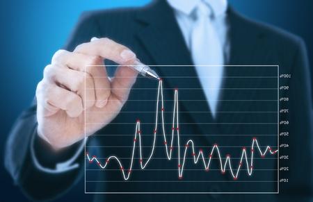 company growth:  businessman writing graph of stock market  Stock Photo