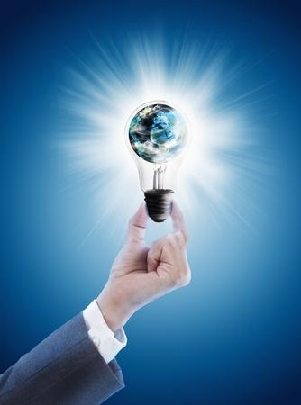 Hand hält einzige Glühbirne mit Globus