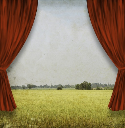 theater stage with red curtains and yellow field photo