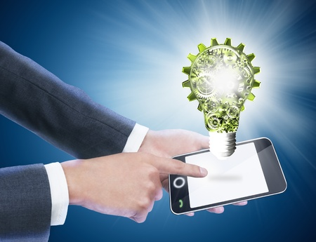 businessman holding mobile phone with light bulb photo