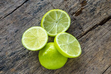 Tahitian limes on a wood background.