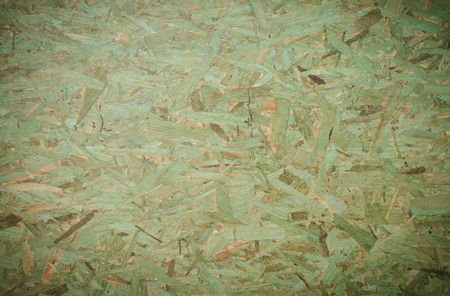 Green background OSB (Oriented Strand Board).