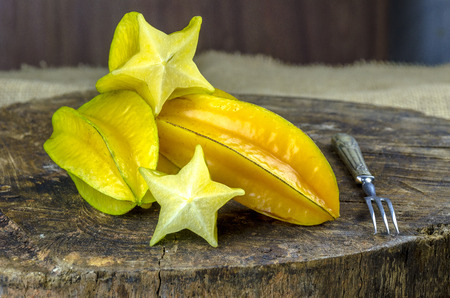 Fresh, juicy and ripe star fruits on a wooden background. Imagens - 119669409