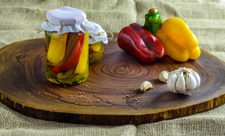 Preserved vegetarian food concept.Canned red, green an yellow peppers in a jar on wooden background. Imagens