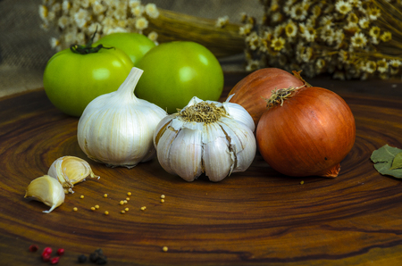 Fresh onions,green tomatos and garlic on the wooden board.