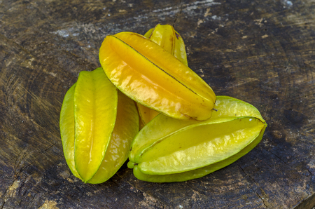 Fresh, juicy and ripe star fruits on a wooden background. Imagens