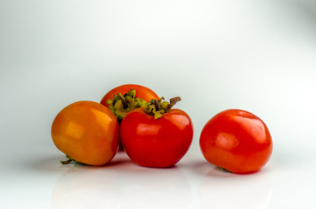 Fresh and juicy persimmon fruits on a white background.