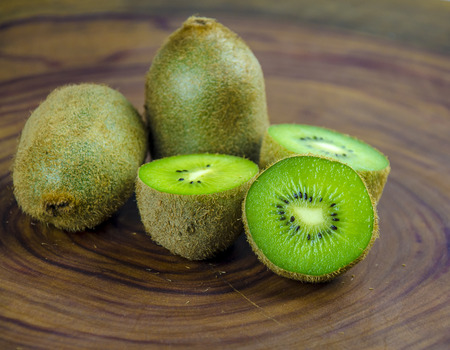 Sliced fresh and juicy kiwi fruit halves on a wooden background. Imagens