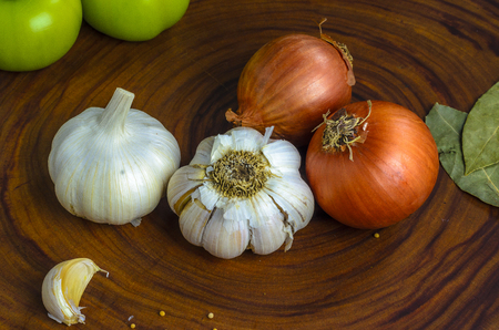 Fresh onions and garlic on the wooden board
