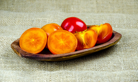 Fresh and juicy persimmon fruits on wooden plate. Imagens