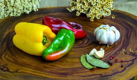 Green , yellow and red bell pepper on athe wood background.