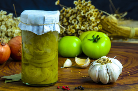 Preserved vegetarian food concept.Canned green onion  in a jar on wooden background.