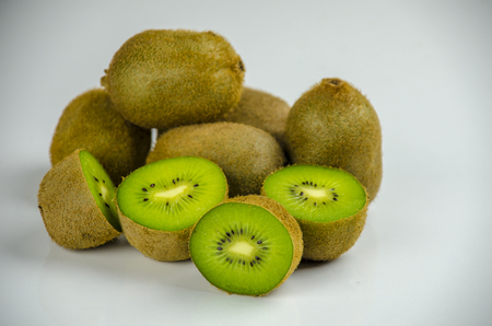 Sliced fresh and juicy kiwi fruit halves on a white background.