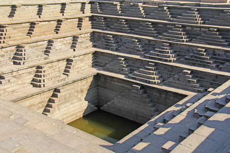 Stepped tank with green water in Pushkarani, Hampi, Karnataka, India. Queens bath. Background geometry. Sacred geometry. Royal enclosure.
