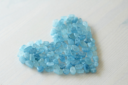 Aquamarine is blue. Blue heart. Natural stone is blue aquamarine. The background is aquamarine. Place for text. Card. Stock Photo