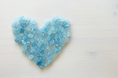Aquamarine is blue. Blue heart. Natural stone is blue aquamarine. The background is aquamarine. Place for text. Card. Foto de archivo