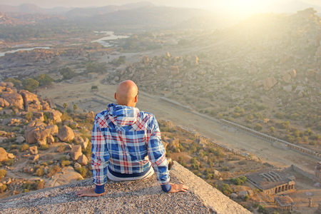 A handsome bald man in glasses sits with his back on a sunset or dawn background in Hampi, India.