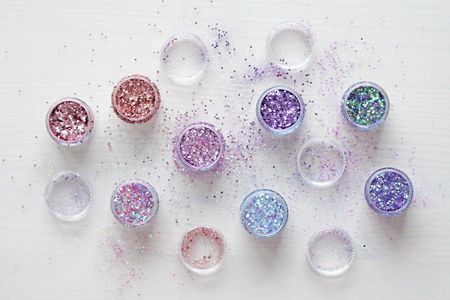 Multi-colored Sequins for the design of nails in a box. Glitter in jars. Foil for nail service. Photo set. Sparkling beauty shimmer, glitter.