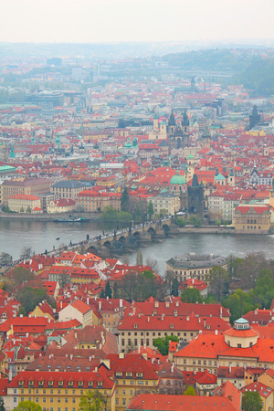 Photo made in Prague. Prague Charles Bridge over the Vltava River and many people, tiled roofs, panoramic view from above Stock Photo