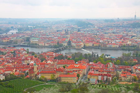 Photo taken in Prague. Prague Charles Bridge over the Vltava River, a horizontal panorama of houses with tiled roofs
