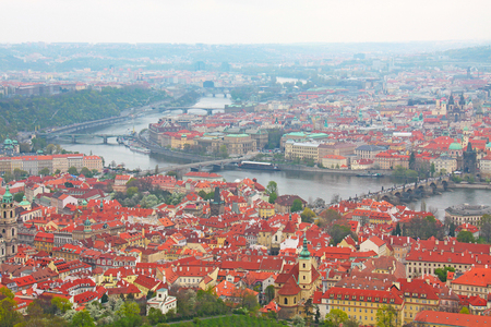 Photo made in ashes, czech republic. Panorama to the city of Prague, Charles Bridge over the Vltava river and houses with tiled roofs view from above Stock Photo