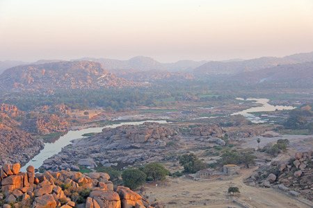 Tungabhadra river in the village of Hampi. Big stone. Tropical exotic landscape. Beautiful sunrise valley. View from above.