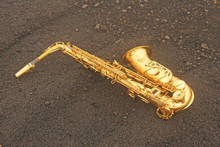 Golden Alto Saxophone Lies on the Black Background. Romantic and Beautiful Saxophone. Place for Text. The Etna volcano. The island of Sicily, Italy. Фото со стока