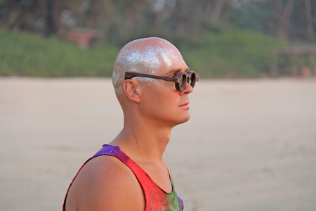 Bald man freak in bright clothes and round glasses at a freak parade or festival, on the beach. India, Goa.