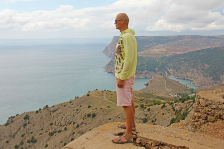 A young bald man is standing on a precipice atop a mountain overlooking the sea and green mountains and looking into the distance. Stock Photo