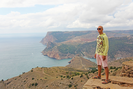 A young bald man is standing on a precipice atop a mountain overlooking the sea and green mountains and looking into the distance. Beautiful landscape. Crimea. Balaclava. Stock Photo