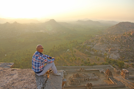 A handsome bald man in glasses sits on a sunset or dawn background in Hampi, on the top of the mountain. Stock Photo