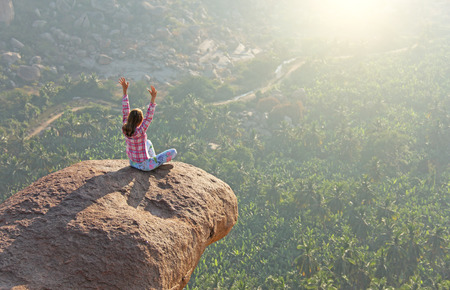 A young girl in a lotus pose is greeting the sun on a background of sunrise or sunset sitting on top of a mountain or on a large rock. Meditation in nature in Hampi. Stock Photo