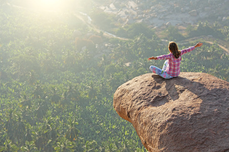 A young girl in a lotus pose is greeting the sun on a background of sunrise or sunset sitting on top of a mountain or on a large rock. Stock Photo