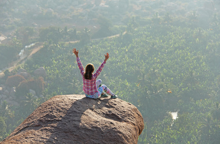 A young girl in a lotus pose is greeting the sun on a background of sunrise or sunset sitting on top of a mountain or on a large rock. Meditation in nature in Hampi. Vijayanagar, karnataka, unesco.