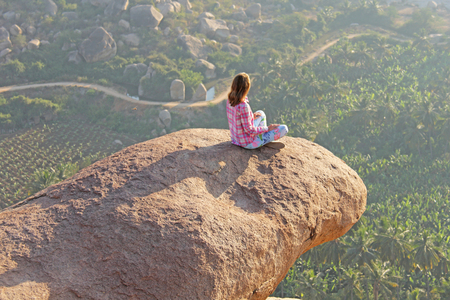 A young girl in a lotus pose on a background of sunrise or sunset sits on top of a mountain or on a large rock.