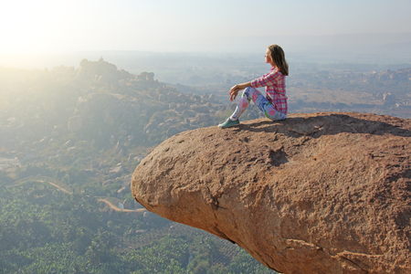 A young girl on a background of sunrise or sunset sits on top of a mountain or on a large rock. Alone with nature. Stock Photo