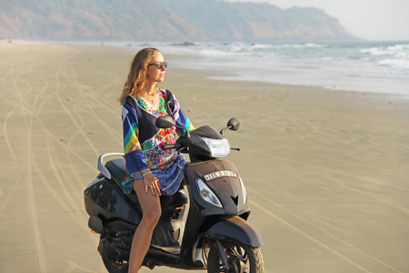 Young beautiful girl with blond hair sits and rides on a black scooter by the sea or beach. Girl on the scooter. India, Goa.