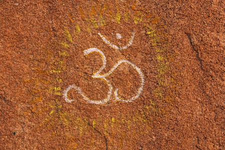 The symbol OM is drawn on a tamboo. Buddhism, yoga, zen. Rock drawing.