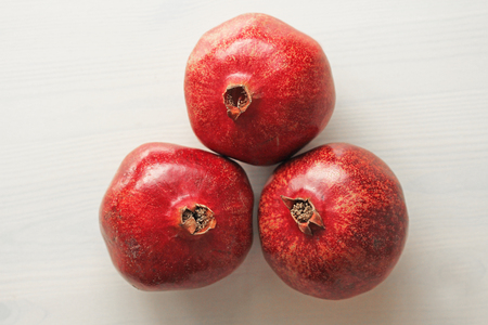 Big Ripe Red Granets or Garnets. Fruits of Red Ripe Pomegranate on the White Background. Vegetarian Concept, Organic Vitamins, Detox. Organic and Benefit Garnet Fruit. Grains of Ripe Pomegranate. Stock Photo